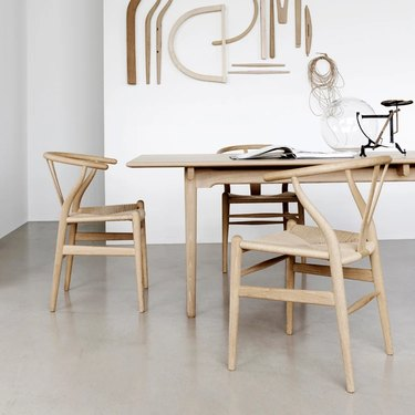 Minimalist dining room idea with wood dining table and chairs with woven seats in white dining room with cement floor