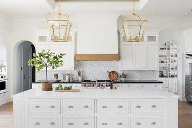 kitchen island decor in white kitchen with subway tile backsplash and wood floor