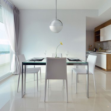 Minimalist dining room idea with chrome globe pendant light in white dining room with white chairs