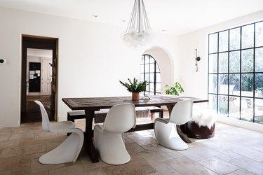 Minimalist dining room idea with Panton chairs at wood dining table on limestone tiled floor