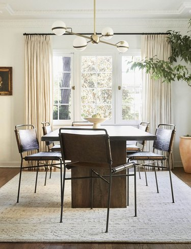 Minimalist dining room idea with industrial-chic dining chair with wood table below modern chandelier