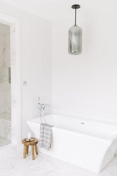 Marble minimalist flooring in white modern bathroom with soaking tub