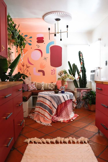 vermillion color kitchen cabinets, terracotta tile floor, art painted on wall, corner built in dining space, textiles over dining table, modern chandelier, plants.