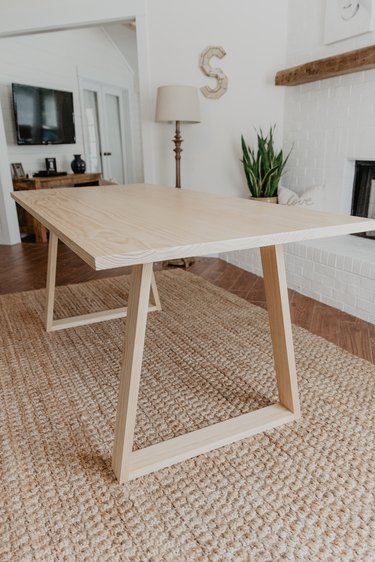 DIY minimalist dining table with angular legs and a wood finish