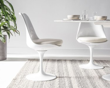 Minimalist dining room idea with Eero Saarinen table with white tulip chairs on textured rug