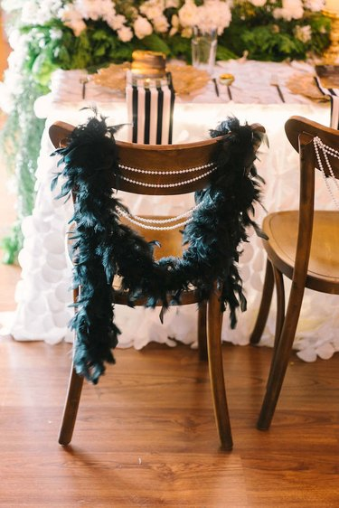 art deco themed party idea with feather boa and pearls draped along back of chairs