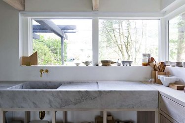 Marble minimalist kitchen sink with wall-mounted brass faucet