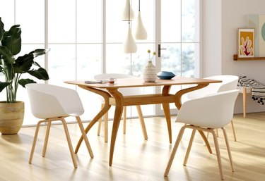 Minimalist dining room idea with midcentury wood table and white chairs with pendant lighting above