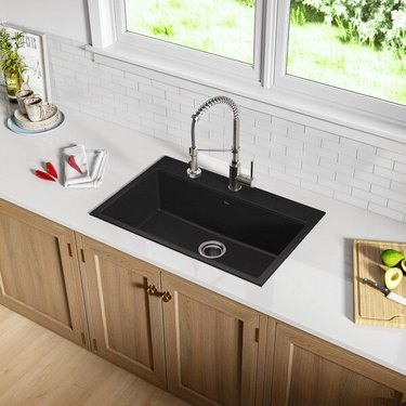 black minimalist kitchen sink in kitchen with white subway tile