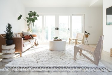 family room flooring ideas with white rug and leather couch