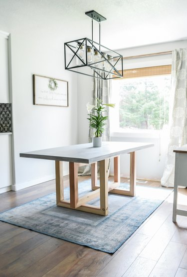 DIY minimalist dining table with concrete top and geometric wood legs