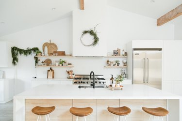 kitchen island decor on wooden footed tray in minimalist kitchen with green wreath