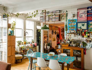 eclectic dining room with vintage green pendant light and antique wood furniture