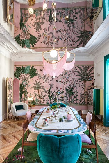 chinoiserie wallpaper in glam dining room with pink-fringed pendant lights
