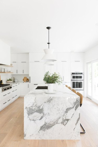 white kitchens with wood floors and marble waterfall island