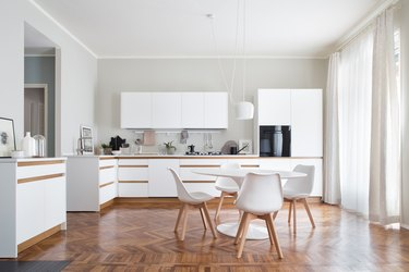 white kitchens with wood floors with scandinavian table and white chairs