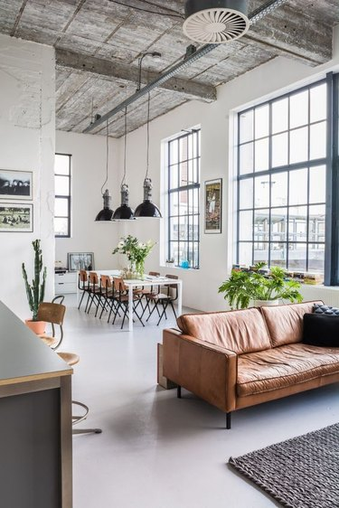open floor plan industrial living room idea with concrete flooring and leather sofa
