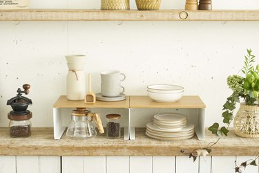 kitchen space with small shelves and kitchen plates and utensils