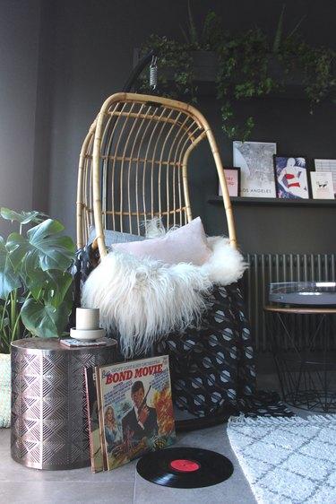 hanging rattan chair in dark gray living room corner idea