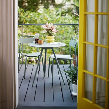 small minimalist balcony idea with green outdoor table and chairs