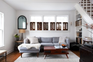 living room with midcentury coffee table, white walls, bookcase