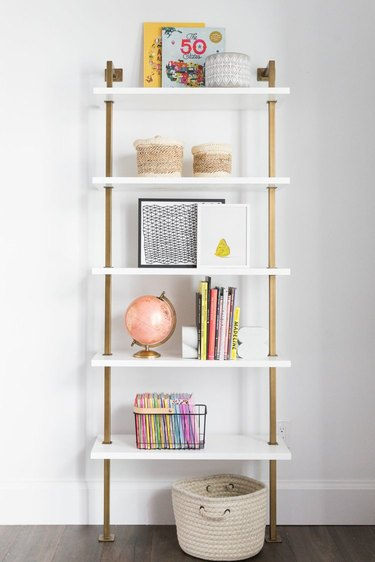Minimalist toy storage idea with white and brass shelf with books and toys