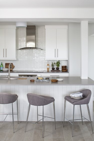 white kitchens with wood floors, gray island, and gray stools