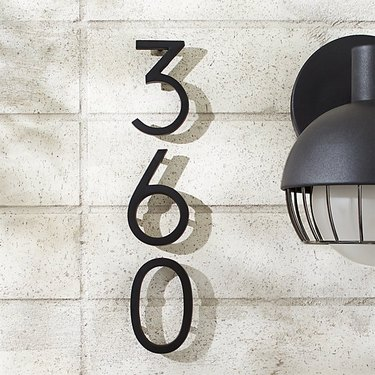 modern house numbers on white brick siding by CB2