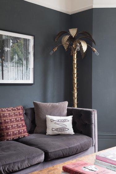 dark gray living room corner idea with statement gold palm tree light