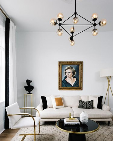 Living room lighting idea with chandelier and vintage painting