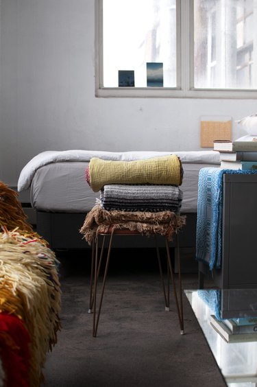 Brooklyn loft with bed and stacked blankets on stool