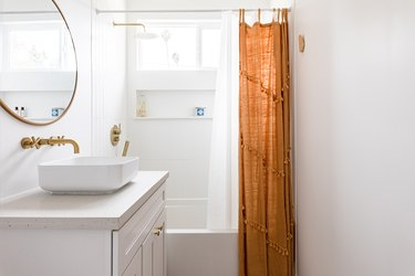 bathroom with bowl sink, circular mirror, brass fixtures and rust-orange shower curtain