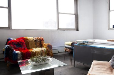 Brooklyn loft with white walls, large windows, and colorful couch