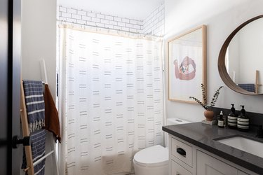 bathroom with shower, toilet, vanity cabinets and circular mirror