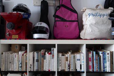 Packed bookshelf with motorcycle helmet and guitar case