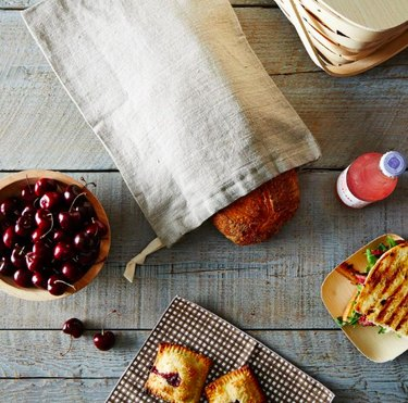 table with various foods and bread in linen bag