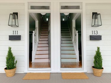 modern house numbers on white siding below wall sconces
