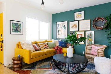 bohemian living room with green accent wall and yellow sofa
