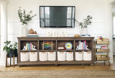Family room toy storage in shelf under TV and white rope bins