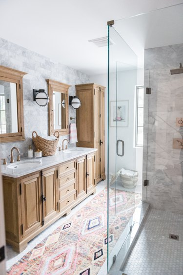 Bathroom rug idea with bohemian flair paired with wood cabinets and glass shower enclosure