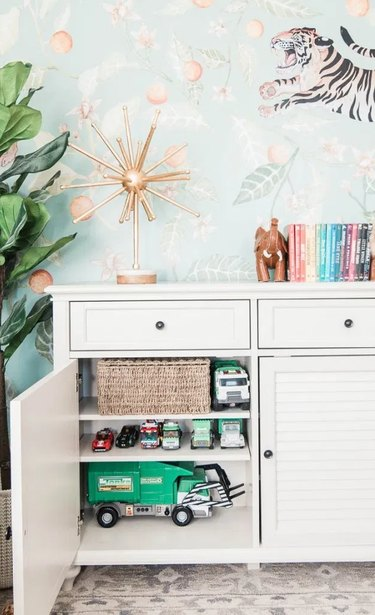 Family room toy storage in white cabinet storing trucks and other toys