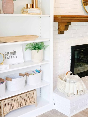 Family room toy storage in white rope baskets and a cane container