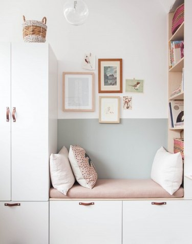 Minimalist room paint colors in bedroom with light green walls, white storage, and pink seat cushion