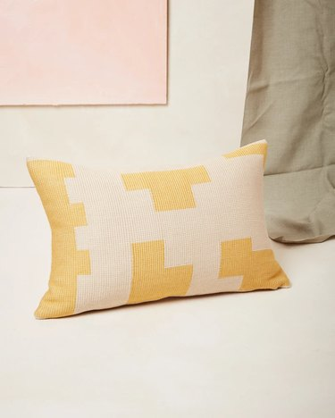 beige and yellow patterned lumbar pillow