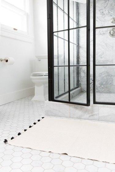 bathroom rug idea in white and black bathroom with hexagonal floor tile