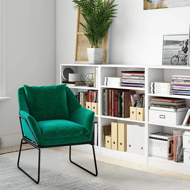 Velvet emerald green armchair with black metal frame
