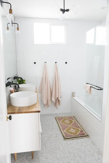 bathroom rug idea in white and pink bathroom with wood countertops and vessel sinks