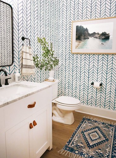 bathroom rug idea with patterned wall paper and wood flooring