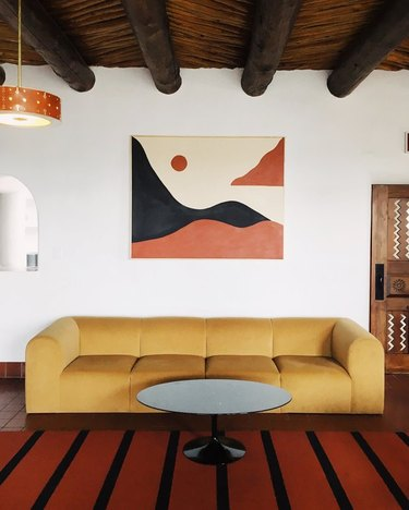 minimalist with color in retro living room with yellow sofa