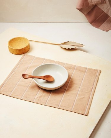 light pastel placemat with dinnerware nearby